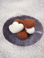 White and brown heart shaped sugar cubes, on blue background