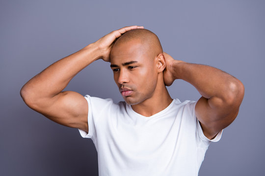 Close up photo dark skin he him his guy hand arm hold bald head looking pensive contemplation concentrated guessing to empty space wearing white t-shirt outfit clothes isolated on grey background