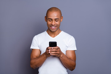 Close up photo strong healthy dark skin he him his macho bald head telephone arms reader foreign pen-friend exciting amazing communication wearing white t-shirt outfit clothes isolated grey background