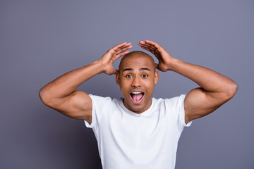Close up photo strong healthy dark skin he him his macho bald head mouth opened yell with all voice hands arms raised wondered wearing white t-shirt outfit clothes isolated grey background