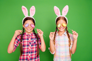 Portrait of two nice adorable lovely funny cheerful cheery positive pre-teen girls wearing checked shirt closing eyes with eggs feast isolated over bright vivid shine green background