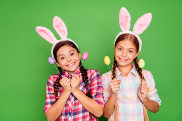 Close up photo of charming with beaming toothy smile white caucasian latin hispanic kids school girls holding colorful eggs in hands isolated bright vivid background