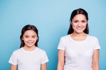 Close up photo two people brown haired mum and small daughter standing straight looking to camera wearing white t-shirts isolated on bright blue background Wall mural