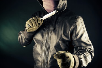 Dangerous criminal hold knife in hand.Large sharp weapon ready for robbery or to commit a homicide.Assassin man.