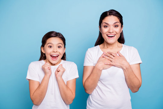 Close up photo pretty two people brown haired mum little daughter eyes mouth opened unbelievable arms point herself win lottery prize wearing white t-shirts isolated bright blue background