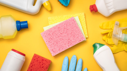 Home cleaning products. Must have concept. Supplies assortment on yellow background. Flat lay.