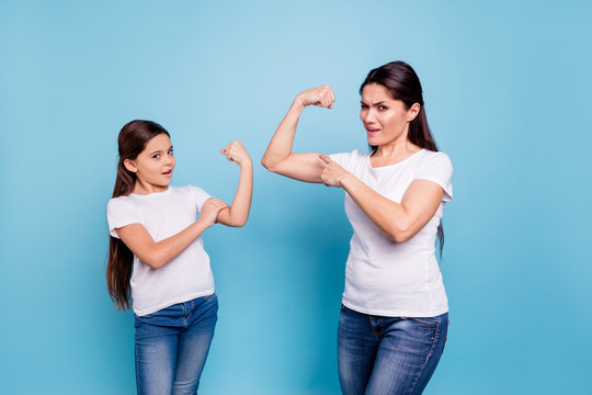 Close up photo I can do it two people brown haired mum mom small little daughter hand on biceps show how powerful girls are wear white t-shirts isolated bright blue background