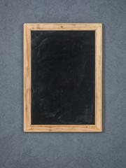 Old chalkboard on grey wall