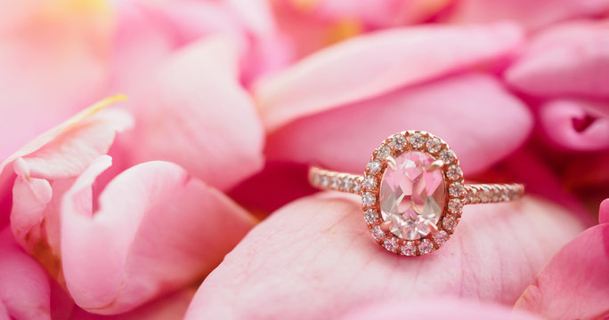 Jewelry pink diamond ring on beautiful rose petal background close up