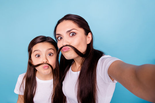 Close up photo amazing beautiful two people brown haired mom small little daughter make take selfies make moustache with curls pretend guy man male wear white t-shirts isolated bright blue background