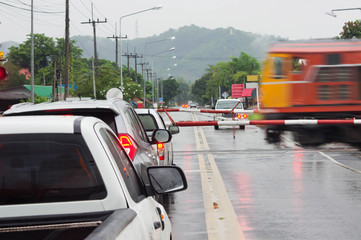 Blurred images of trains moving through bulkheads with vehicles waiting to stop while it rains.
