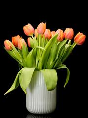 Orange tulips bouquet in white vase on black background