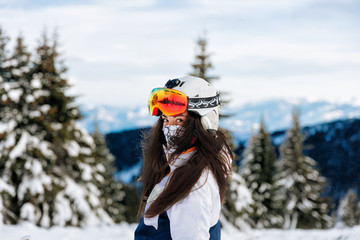 Ski, skier, sun and winter fun - woman enjoying ski vacation. Sport, leisure and people concept - happy young woman in ski goggles outdoors. Ski resort - Image