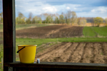 Yellow bucket next to the plowed field.