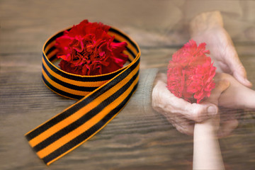 Red carnations and St. George ribbon on a wooden background / St. George ribbon-a symbol of the great Victory/Victory day. The child's hands and the veteran. Concept of Memory after the war.