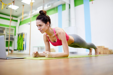 Full length portrait of strong young woman doing plank exercise during workout in fitness club,...