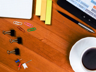 Desk with scattered office supplies, a cup of coffee and a tablet