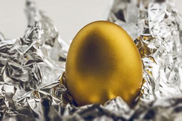 Image of shiny golden egg on silver foil