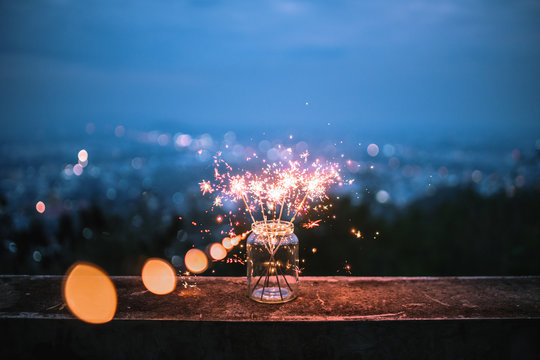 Sparklers in a glass jar that bokeh cities background.