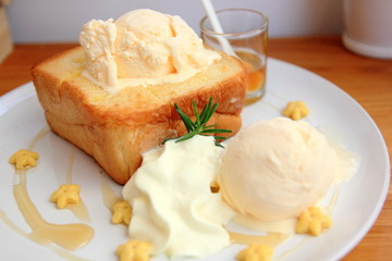 Honey Toast, a square toast baking and topped with vanilla ice cream and honey sauce served and whip cream. Top view.