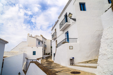 Stunning traditional architecture with white houses with blue windows and a small alley lane between under a sunny sky in frigiliana in spain
