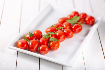 Healthy cherry tomatoes on  white wooden background