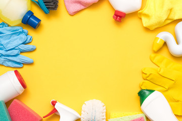 House cleaning products on yellow background. Assorted variety of supplies frame.
