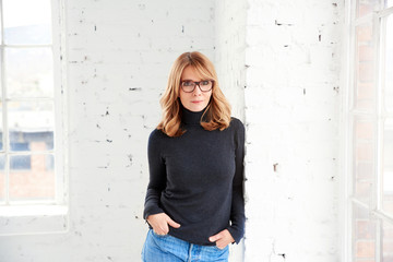 Portrait of attractive woman wearing roll neck sweater and jeans while looking at camera and smiling