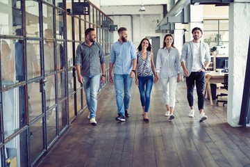 On the way to business meeting. Full length of young modern people in smart casual wear having a discussion while walking through the office.