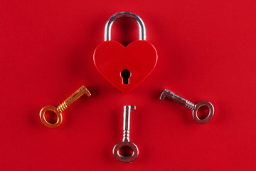 The concept of female infidelity. A heart shaped lock and three keys to it on a red background.