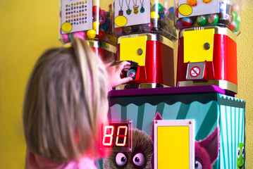 The child picks up a gift in the machine with toys