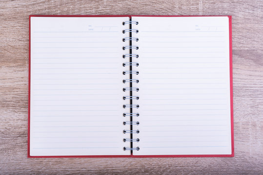 Top view of Open diary  or note book put on wooden table.