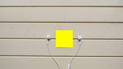 Wall Mural - earphone with post it on woodbackground