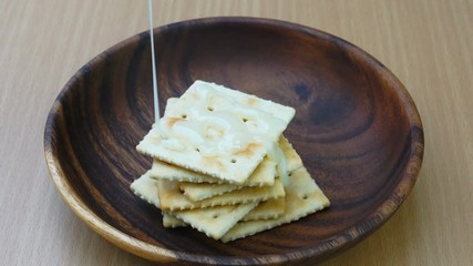 Fototapete - Pouring condensed milk on the pile of crackers in a wooden plate on the table