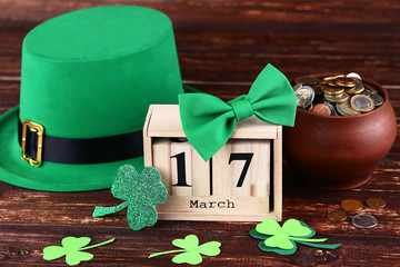 St. Patrick's Day. Green hat with clover leafs, wooden calendar and coins