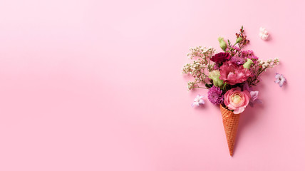 Summer minimal concept. Ice cream cone with pink flowers and leaves on punchy pastel background. Flat lay. Top view. Banner. Creative layout