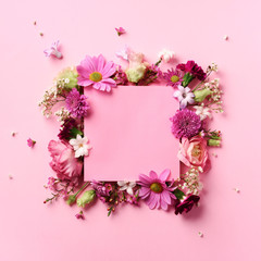 Frame of pink flowers over punchy pastel background. Valentines day, Woman day concept. Spring or summer banner with copy space