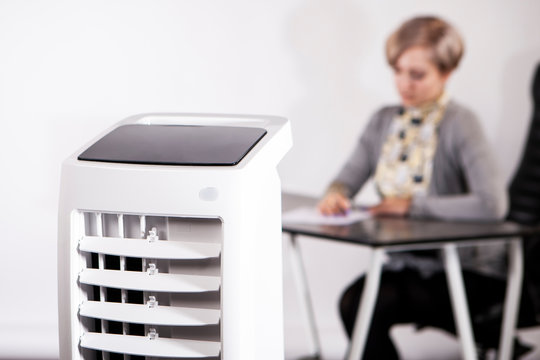 Air purifier in the office. A woman works in an office with air conditioning. Caring for employees. Air conditioning facilities. Outdoor air conditioning.
