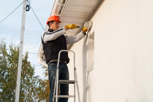 electrician installs a lamp