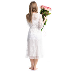 Woman in dress with flowers roses in hand on white background isolation, back view