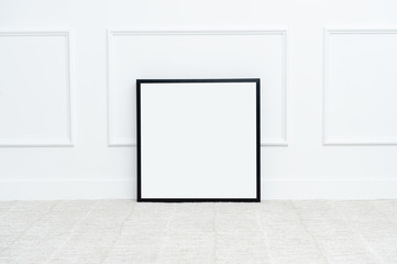 There are beautiful flowers and various objects near the rectangle blank picture frame in front of white wall on the carpet living room.