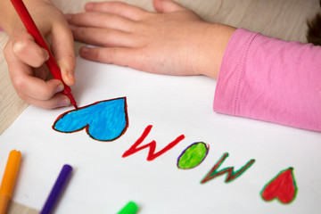 View from above of childs hands drawing with colorful crayons I love Mom on white paper. Art education, creativity concept.