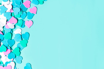 Flat lay of colorful bright blue paper background with pink hearts, copy space. Valentine Day, Greeting card
