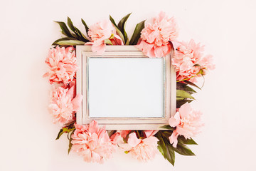 Pastel wooden frame decorated with coral peonies flowers, empty space for text