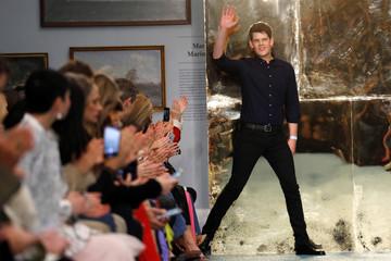 Designer Wes Gordon waves after presenting the Carolina Herrera collection during New York Fashion Week