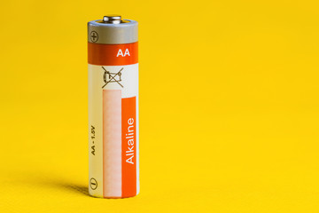 1.5 volt alkaline battery, AA size, on yellow background. Close up.