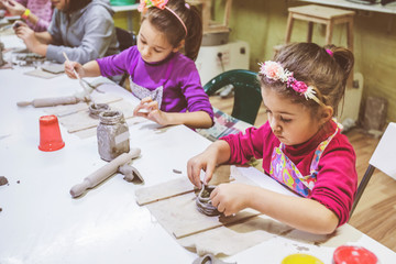 Little Girl At Pottery Workshop Working With Clay
