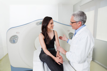 Doctor explains to the young lady in the room of head scan at hospital