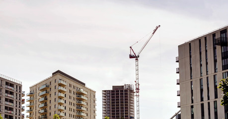 new apartments under construction site with Industrial crane, a high building