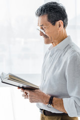 retired man in glasses standing and reading book at home